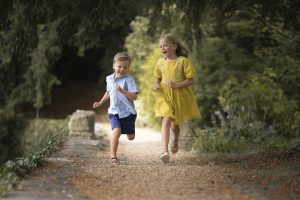 siblings running towards the camera looking very happy